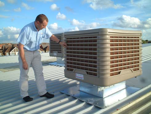 Handyman servicing an evaporative air conditioning unit in perth