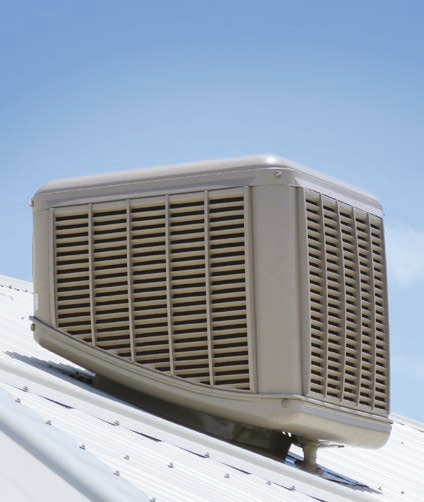 White evaporative cooler at the top of a roof on a sunny day